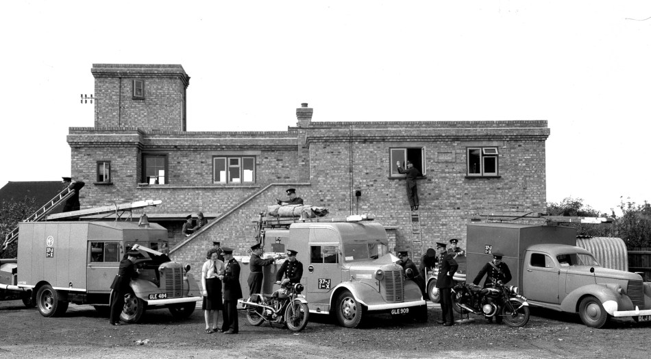 Firefighters stand outside a small brick fire station with three vans and two motobikes.