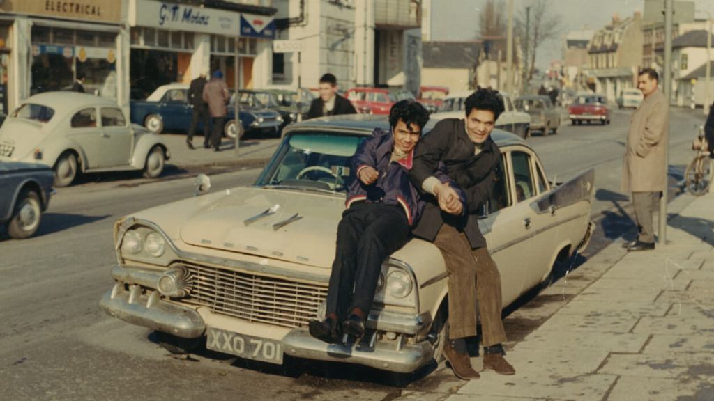 Two young men sit on the hood of a car in the street
