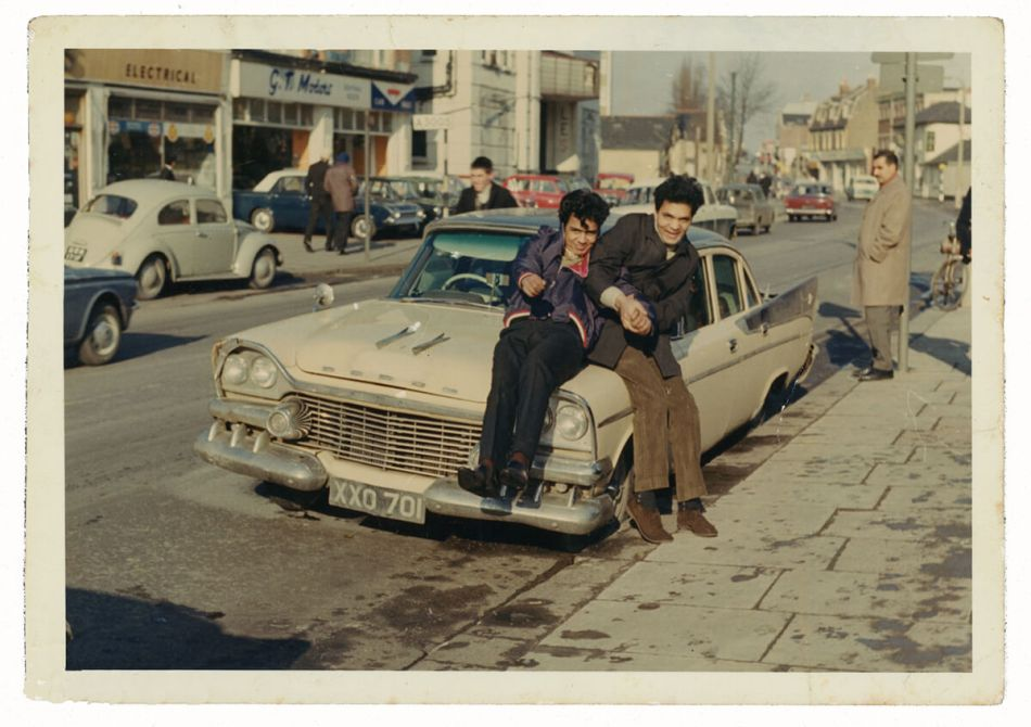 Two teenage boys sit on the hood of a car