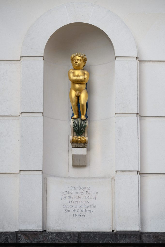 Small gold statue of a young boy on a plinth on a white building. The inscription: This boy is in memory put up for the late Fire of London occasioned by the Sin of Gluttony, 1666.' is below him.