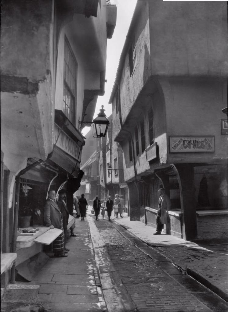 A narrow cobbled street with buildings either side almost touching at the top