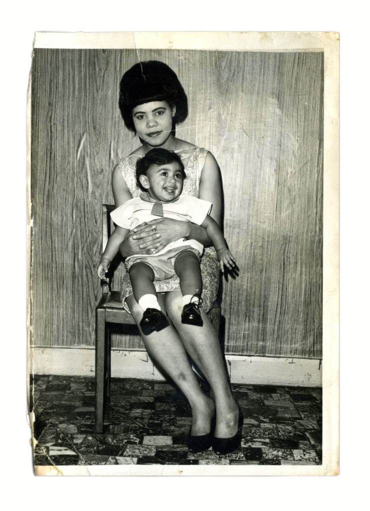 A young woman holds a small boy on her lap.
