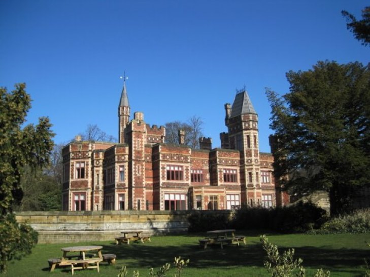 A red brick house with turrets, in front of the building are benches in a park