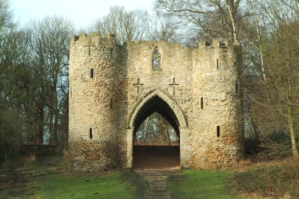 A castle structure with two towers and a  gateway surrounded by trees