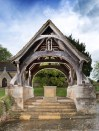Lych-gate, St Faith's church, Overbury, Worcestershire. Unveiled 12 September 1921. Upgraded to Grade II*. The lych-gate was designed by Herbert Baker for the Holland-Martin family of Overbury Court. Their 19 year-old son, Geoffrey Holland-Martin, was killed in action in France, March 1918 and had no known grave. There are many lych-gate memorials in England, but this is an exceptionally fine example reflecting Baker's interest in symbolism, with its carved angels and central coffin rest reminiscent of the empty tomb of a cenotaph. The heavy oak timberwork, carved with biblical quotes, evokes an ancient agricultural building. Tiles for the roof were reputedly recycled from old buildings in the village. The coffin rest carries a main inscription remembering the fallen of Overbury, along with their names. Its north side bears a quotation from William Blake's poem 'Jerusalem', I WILL NOT CEASE/ FROM MENTAL FIGHT/ NOR SHALL MY SWORD/ SLEEP IN MY HAND/ TILL WE HAVE BUILT/ JERUSALEM/ IN ENGLANDS GREEN/ AND PLEASANT LAND.