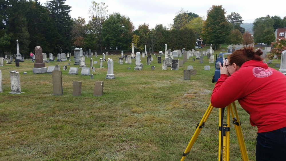 One student using total station mapping device on tripod while another student stands on the other end of a cemetery with the mapping prism on a pole