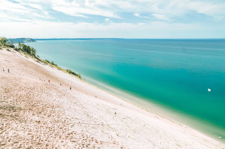 Lake Michigan Overlook Sleeping Bear Dunes stretching farther than you can see. | herlifeadventures.blog | #camping #usdestinations #sleepingbeardunes #nationallakeshore #travelhacks #travelguide #adventuretravel #roadtrip #nationalpark #nationalparkroadtrip #michigantravel #greatlakes #ustravel #summer #bucketlist