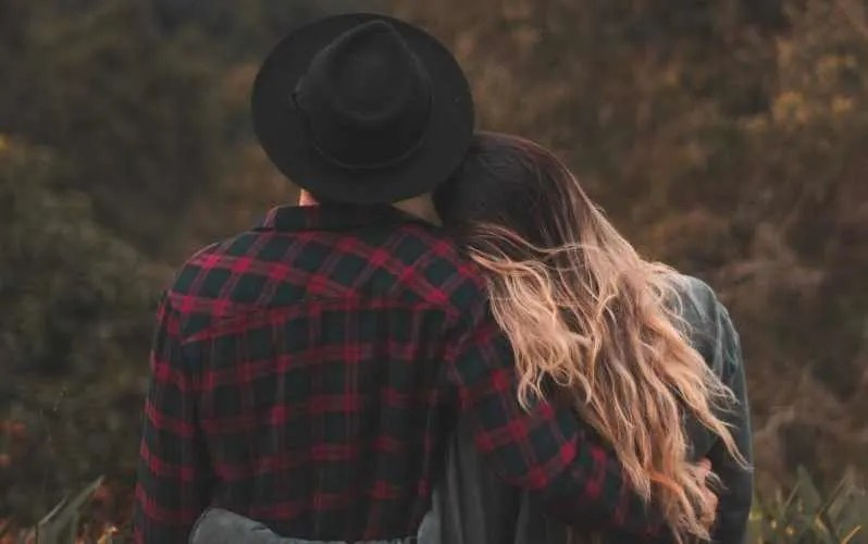 Man and woman with arms around each other facing nature background