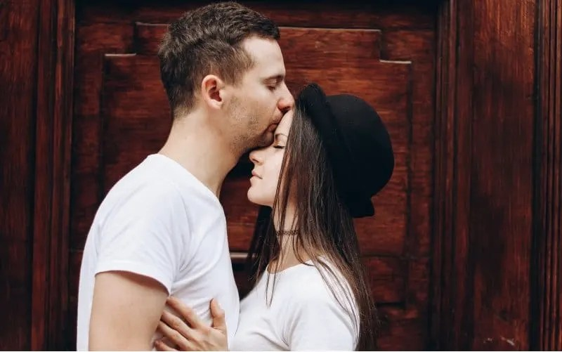 Man kissing woman on her forhead