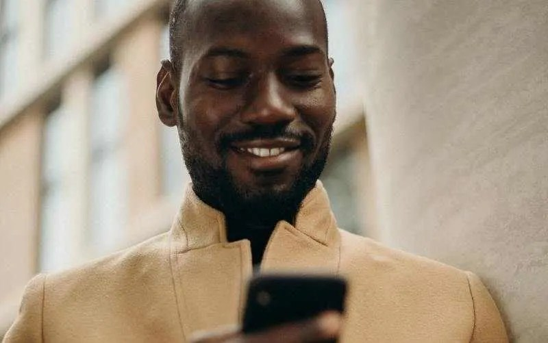 Man smiling and texting on his phone