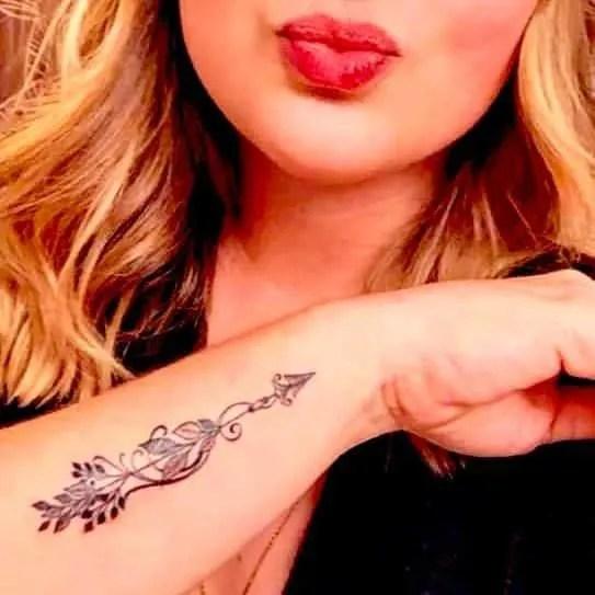 an elegant arrow wrist tattoo on woman`s hand