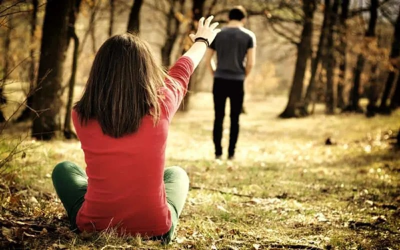Young couple breaking up in a forest