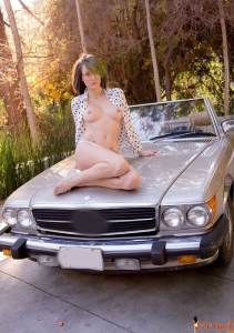 Malena Morgan showing her natural boobs and sexy legs on car's bonnet.