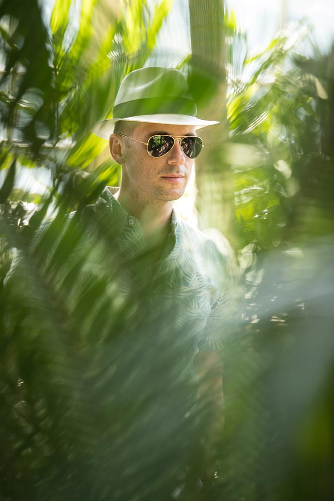 looking-through-palm-trees-casual-mens-summer-outfit-ideas-printed-shirt-panama-hat-aviator-sunglasses