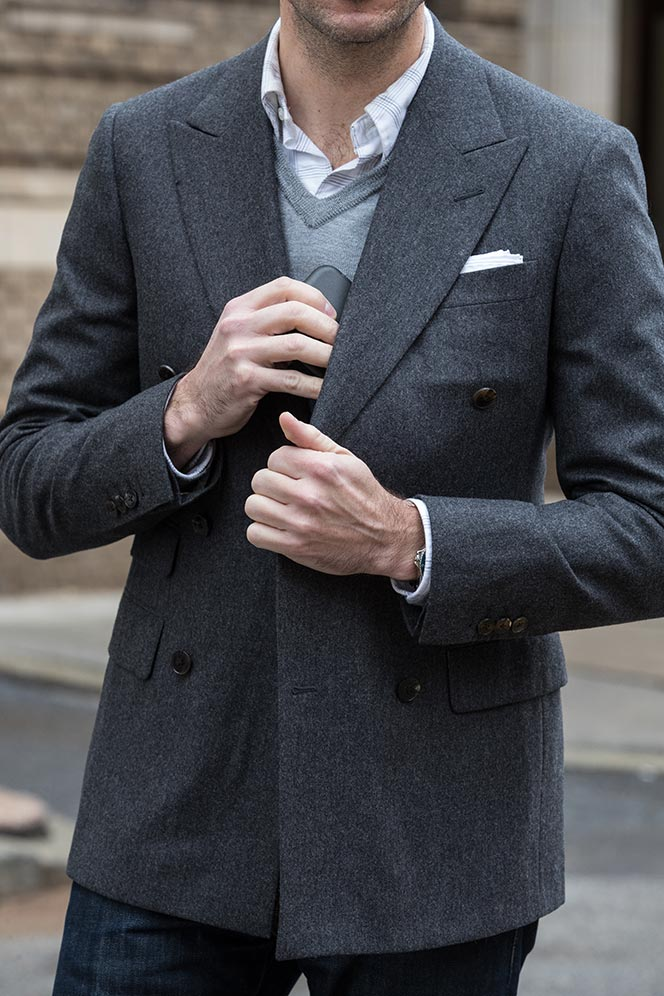 grey-flannel-double-breasted-blazer-layered-sweater-shirt-putting-phone-into-inside-jacket-pocket