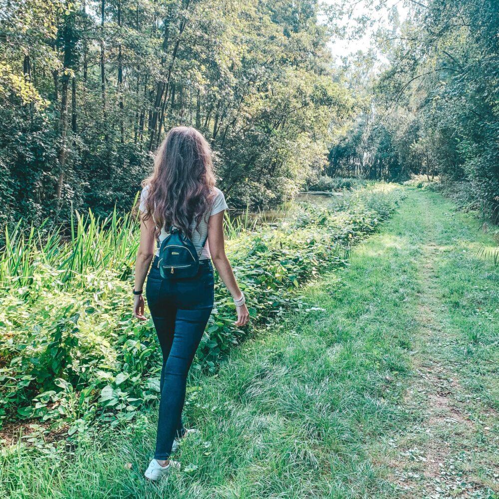 Het Gezinsleven - Lifestyle - Sporten - Wandelen is gezond - vrouw wandelt langs een beekje