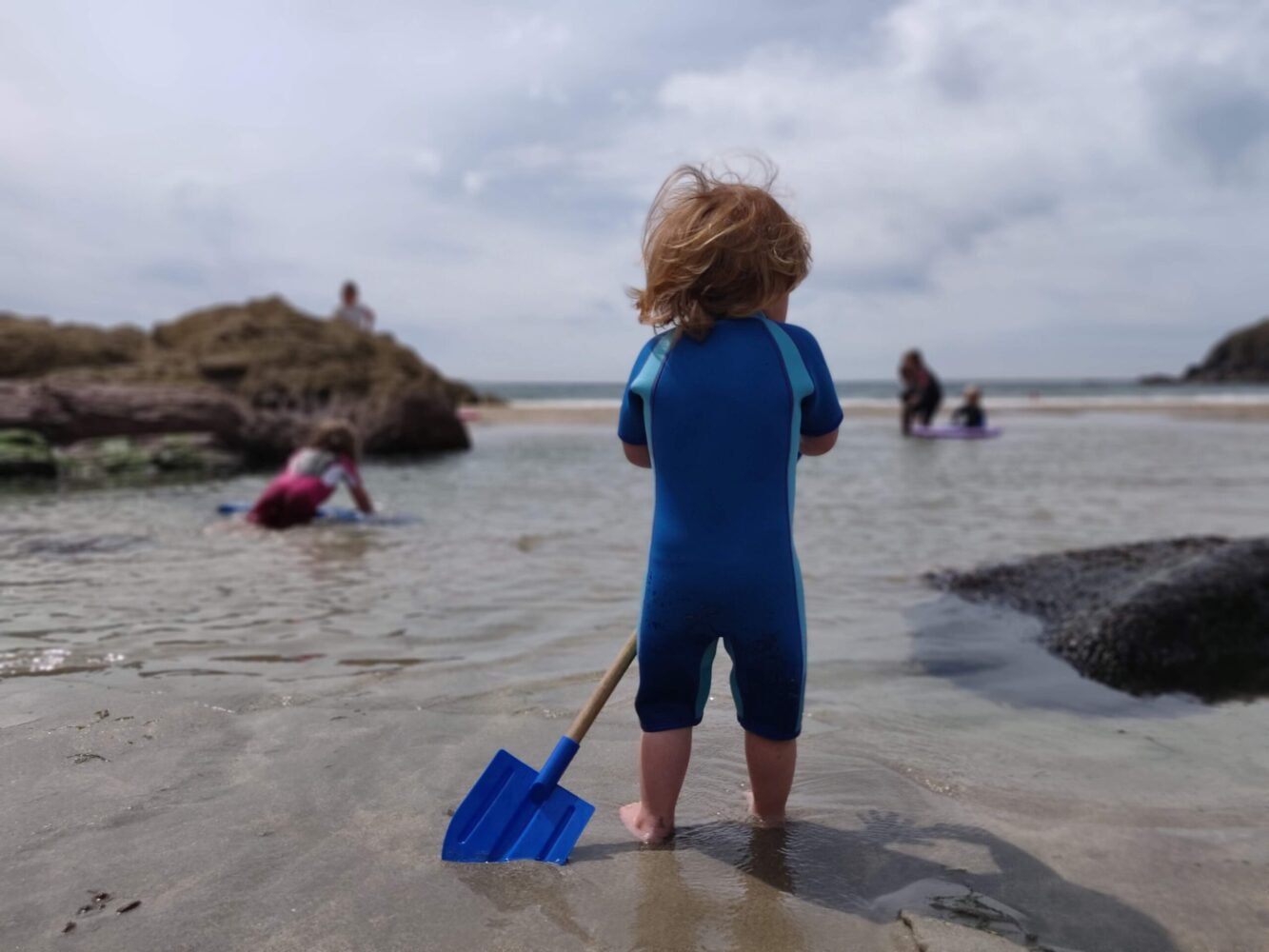 Het Gezinsleven - Moeder en Kind - Moeders - Zonbescherming voor kinderen - Jongen speelt in UV-werende kleding op het strand