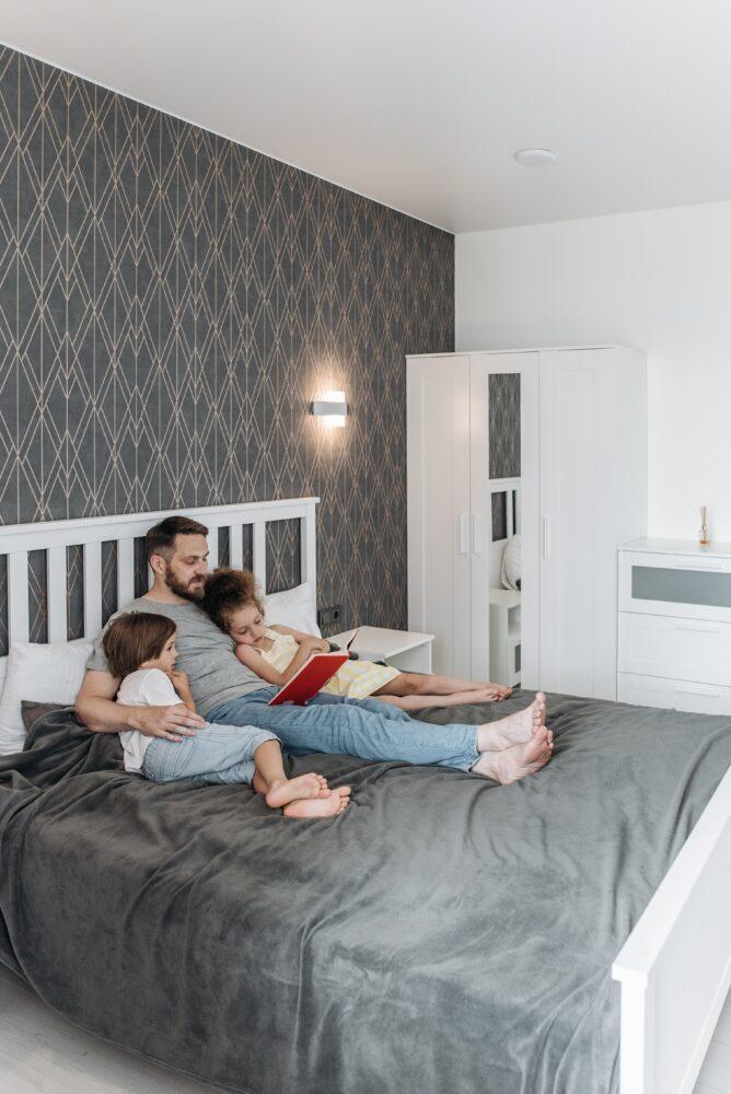 Het Gezinsleven - Moeder en Kind - Kinderen 1-4 jaar - Gentle Parenting en alles wat je er over moet weten! - Man leest boek op bed met kinderen