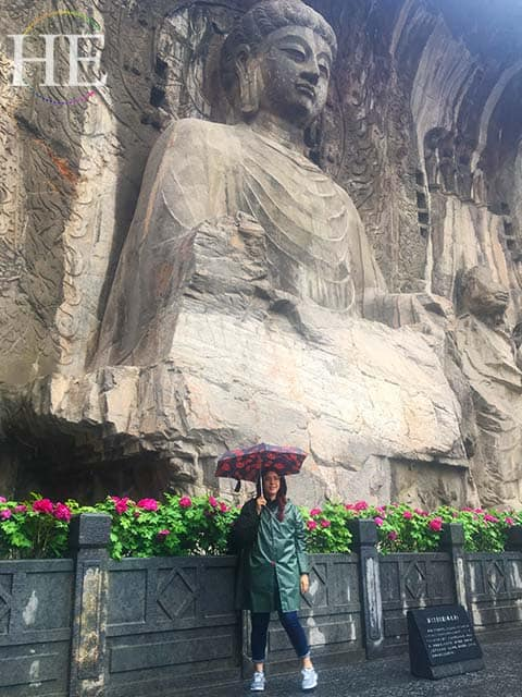 julianne stands in front of the largest buddha statue at longmen grottoes in luoyang china