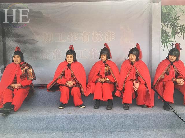 women performers dress in vibrant red costumes at a park in zhengzhou china