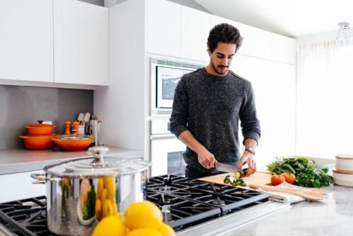 cuisiner un plat dans une cuisine rangée