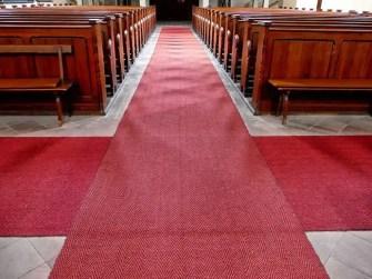 Roter Teppich über Kreuz in der Kirche