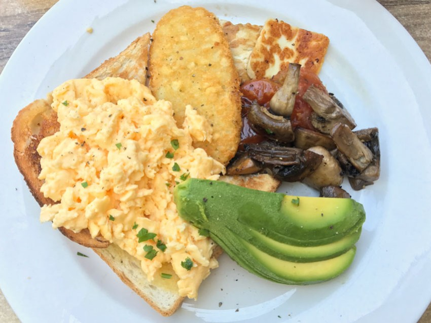My meal with avocado, hash brown, mushrooms, scrambled eggs, halloumi and tomato relish