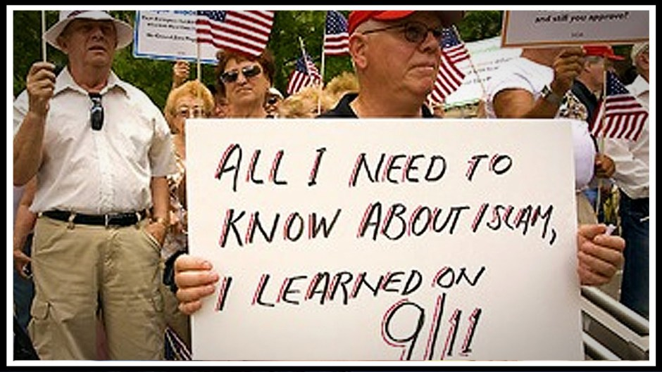 """A protester at a rally attacking New York Mayor Bloomberg holds a sign that reads """"ALL I NEED TO KNOW ABOUT ISLAM, I LEARNED ON 9/11"""""""
