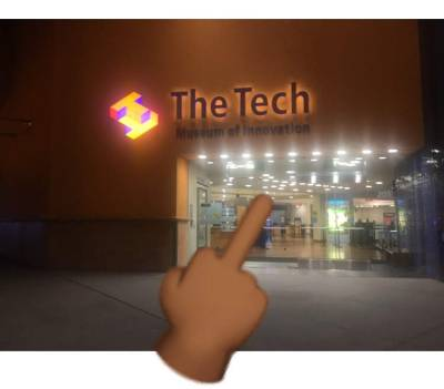 nighttime picture of the tech museum with a middle finger emoji over it
