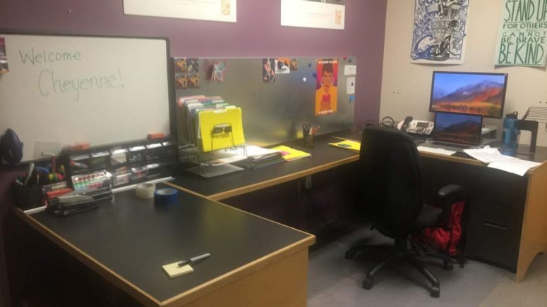 picture of my office; 3 desks in the shape of a U with a desk chair and monitor on one side and whiteboard against the wall