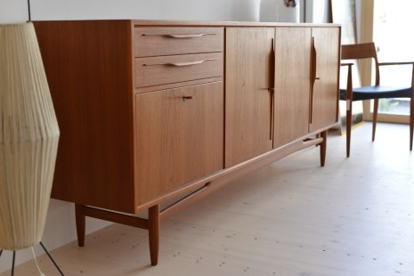 Swiss Teak Sideboard with a chair and a lamp