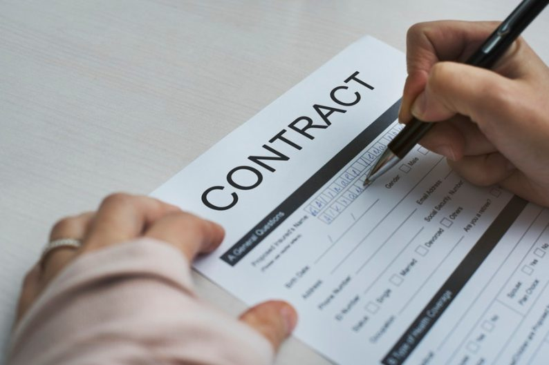 Hands writing contract