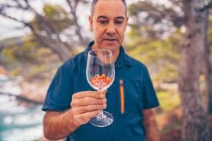 Evarist March from NaturalWalks smelling wildflowers in a wine glass | Costa Brava's Coastline