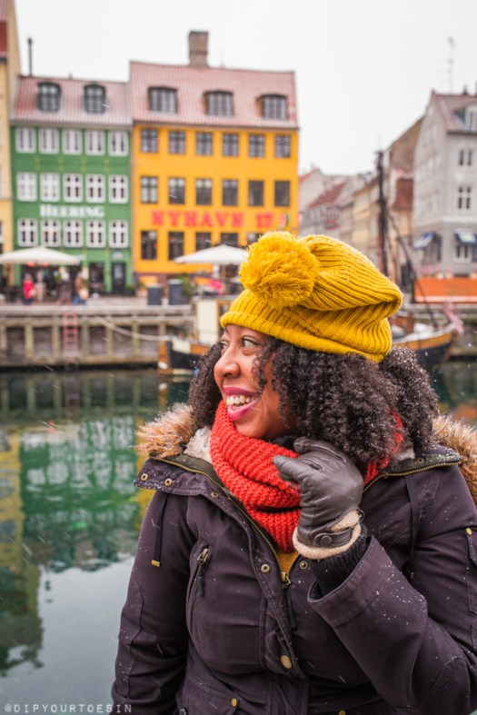 Eulanda standing by river bank at Nyhavn with colourful houses in background | Copenhagen, Denmark