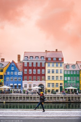 Eulanda walking along Nyhavn with colourful houses in background | Dear Copenhagen