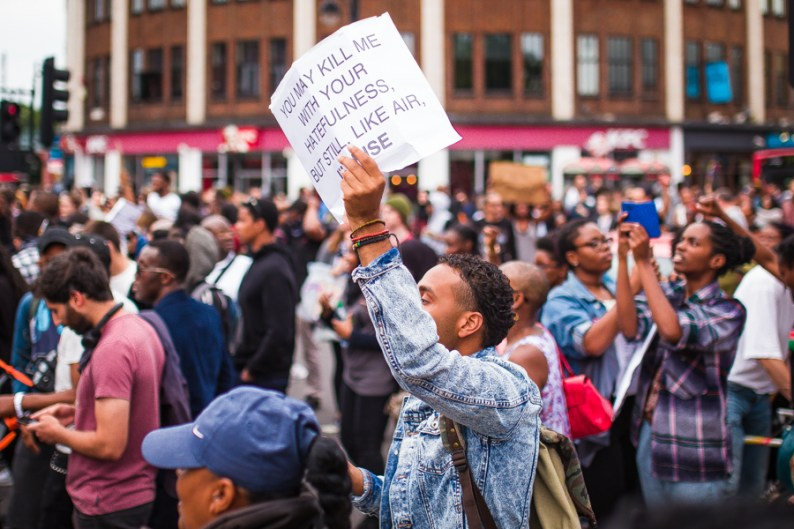Black man holding up protest sign reading: You May Kill Me With Your Hatefulness But Still, Like Air, I Rise