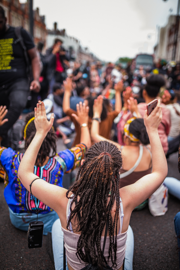 """Protesters sitting on the road with """"Hands Up! Don't Shoot"""" posture 