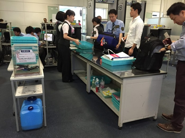 security check at tokyo's haneda airport. the blue jug at bottom left is to dump liquids above 150ml.