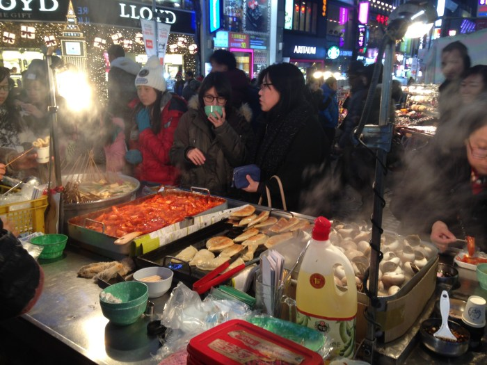 some girls devouring street food in myeongdong, a central shopping area.