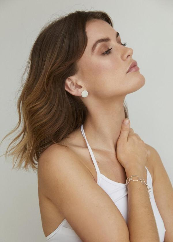 Woman elegantly wears a hypoallergenic Contemporary Disc Stud.