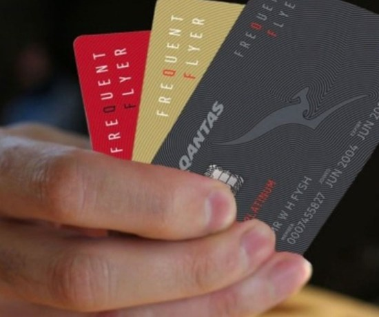 Qantas Frequent Flyer Program cards in a mans hand