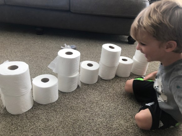 Preschooler practicing patterns and counting with toilet paper rolls.