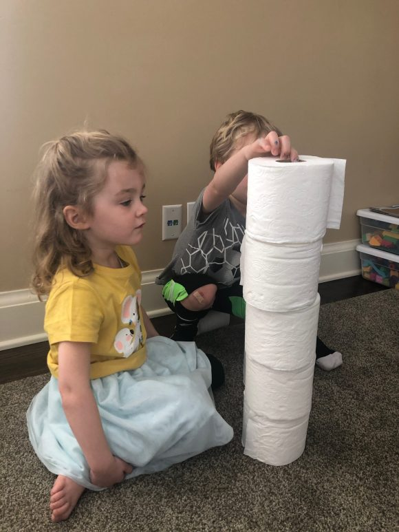 Preschoolers building towers 5 toilet paper rolls high as part of the preschool counting activity.