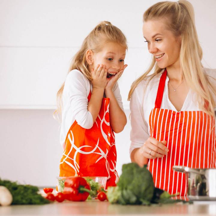 girl excited for dinner watching her mom cook