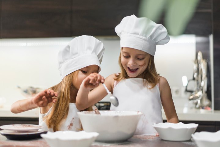 sisters wearing chef's hats and cooking dinner together