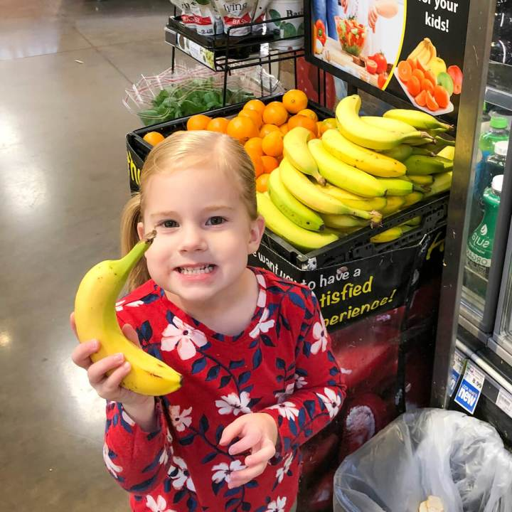 toddler girl selecting fresh fruit from the grocery store