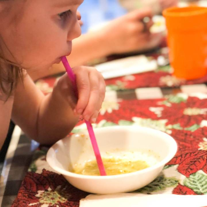 toddler drinking soup with a straw