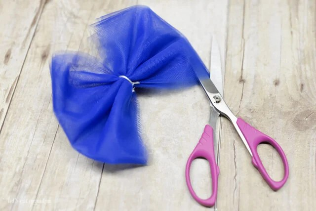blue tulle tied in a bow and scissors cutting sides to separate layers