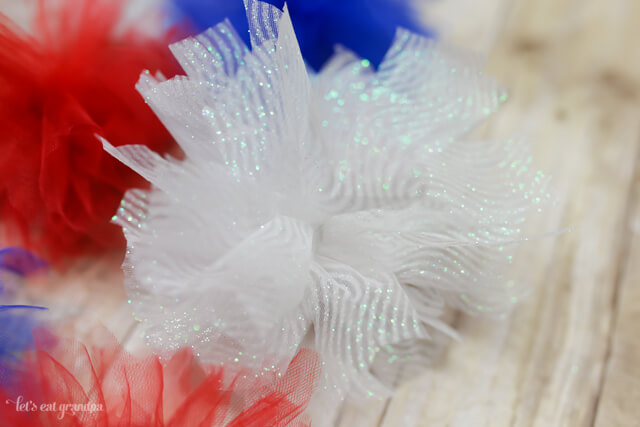 closeup of red, white, and blue firework poofs from tulle
