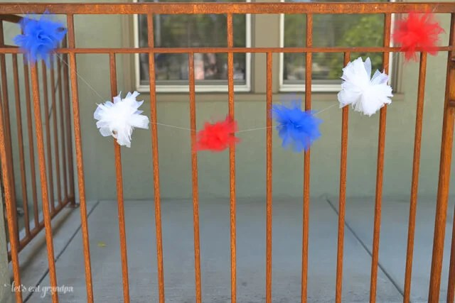 red, white, and blue tulle DIY firework poofs strung on fence